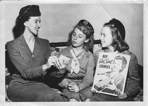 Girl Scouts and troop leader with cookie sign 1960