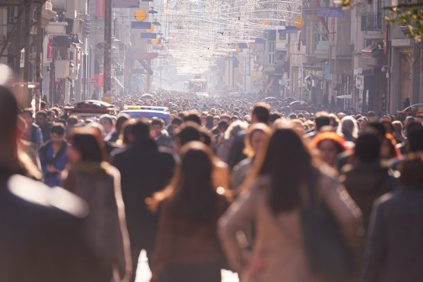 crowd of people walking down busy city street