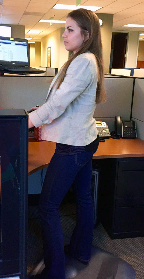Emily Binder standing on ergonomic mat at standing desk