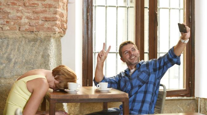 man ignoring woman while taking selfie